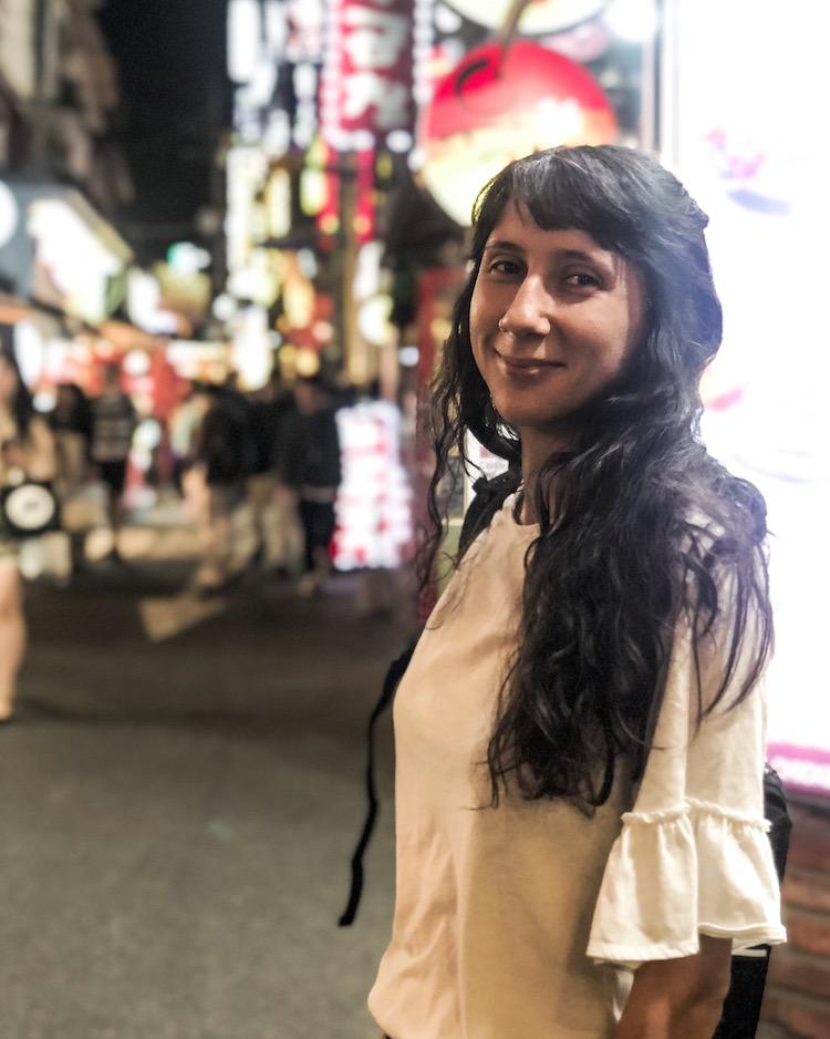 Girl smiling against bright lights in South Korea